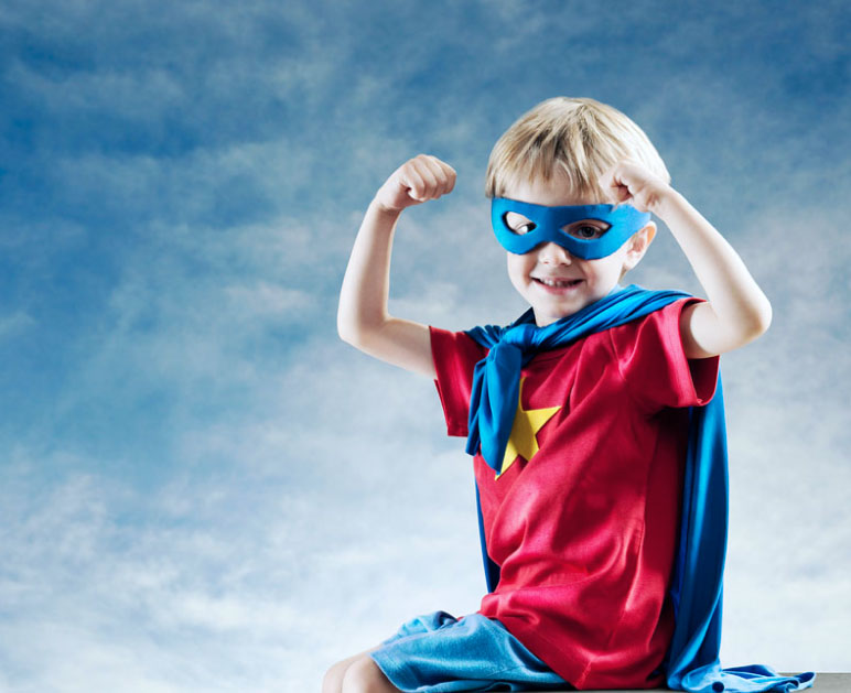 Boy flexing in superhero outfit