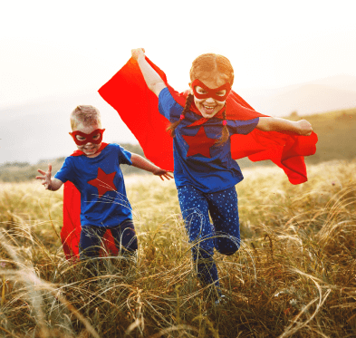 Superhero kids running in field of tall grass